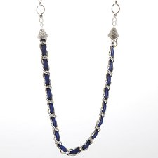 Ett långt silverpläterat kedjehalsband med olika stora kedjor och med ett långt mörkt lila band i